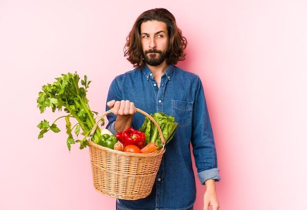 Jonge man plukken biologische groenten uit zijn tuin geïsoleerd verward, twijfelachtig en onzeker. Premium Foto