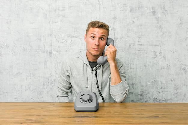 Jonge man praten op een vintage telefoon haalt schouders op en open ogen verward. Premium Foto
