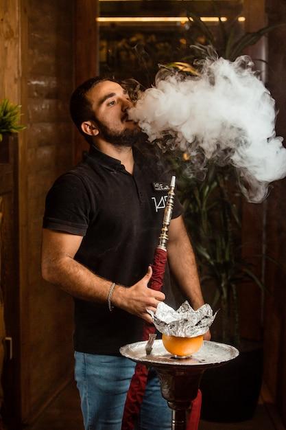 Jonge man rookt waterpijp met sinaasappel Gratis Foto