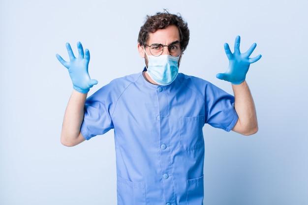 Jonge man schreeuwen in paniek of woede, geschokt, doodsbang of woedend, met de handen naast het hoofd. coronavirus concept Premium Foto