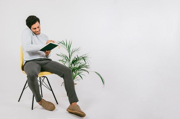 Jonge man schrijven op zijn dagboek en praten over de telefoon Gratis Foto