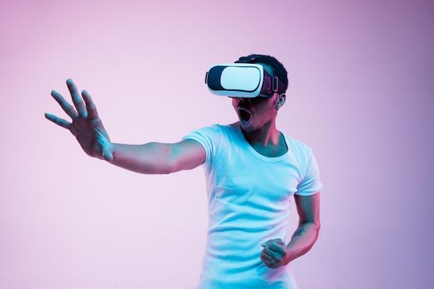 Jonge man spelen in vr-bril in neonlicht Gratis Foto