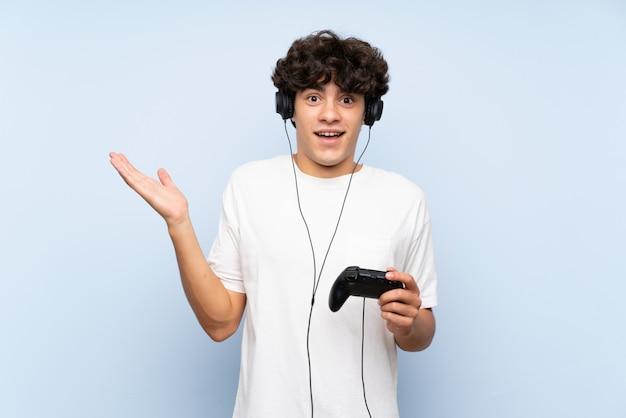 Jonge man spelen met een video game controller over geïsoleerde blauwe muur met geschokte gelaatsuitdrukking Premium Foto