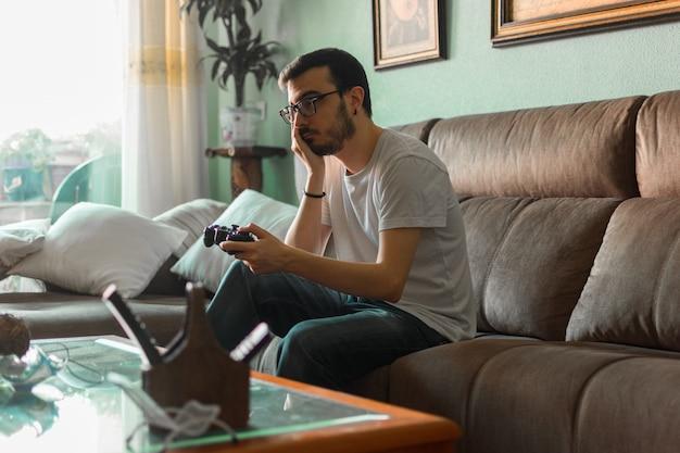 Jonge man spelen videogame bedrijf draadloze controller Premium Foto