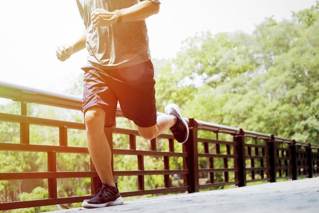 Jonge man sporten en joggen, rennen in een park. Gratis Foto