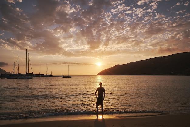 Jonge man staande voor de zee in amorgos-eiland, griekenland bij zonsondergang Gratis Foto