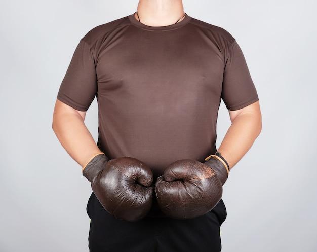 Jonge man staat het dragen van zeer oude vintage bruine bokshandschoenen op zijn handen Premium Foto