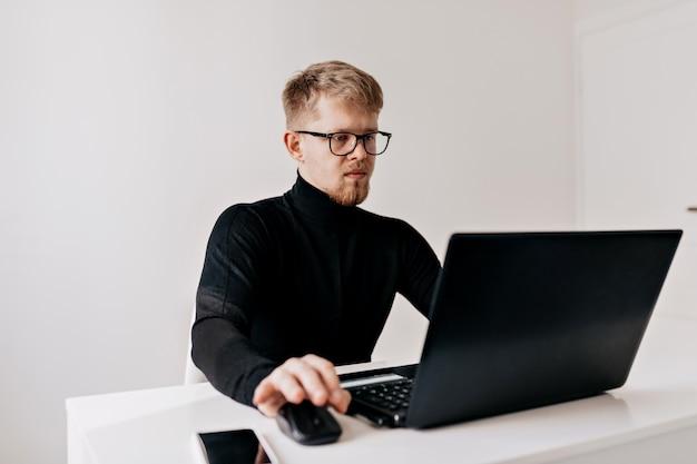 Jonge man teamleider. zelfverzekerde jonge man aan het werk op zijn desktop met laptop en kijken met een glimlach in zijn lichte kantoor. Gratis Foto