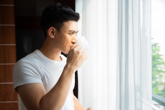 Jonge man thuis koffie drinken Gratis Foto