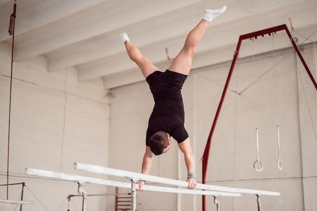 Jonge man training op parallelle staven Premium Foto