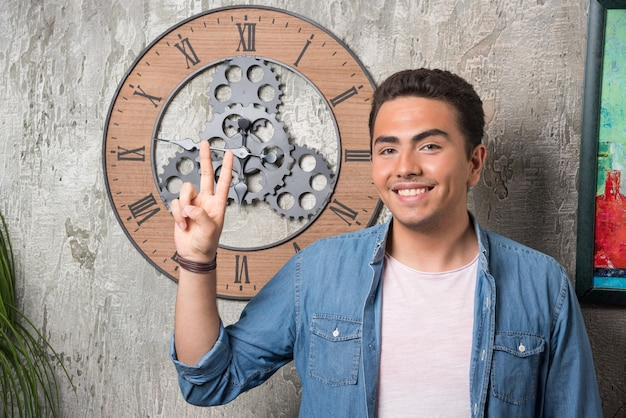 Jonge man twee vingers opdagen en poseren op marmeren achtergrond. hoge kwaliteit foto Gratis Foto