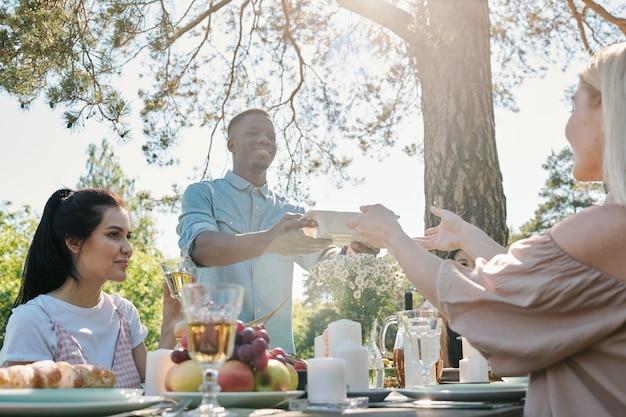 Jonge man van afrikaanse afkomst die container met voedsel uit handen van zijn vriendin over de tafel geserveerd tijdens het diner buiten onder dennenboom Premium Foto