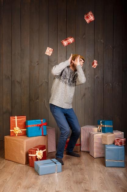 Jonge man verbergen voor vallende kerstcadeaus over houten oppervlak Gratis Foto
