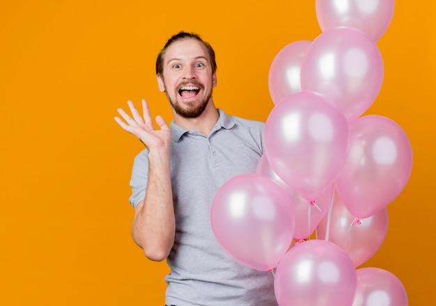 Jonge man viert verjaardagsfeestje bedrijf bos van balloonshapy en opgewonden glimlachend vrolijk staande over oranje muur Gratis Foto