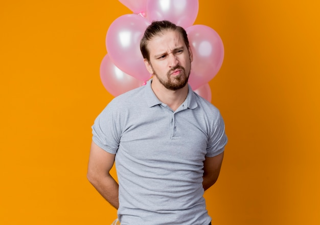 Jonge man viert verjaardagsfeestje met bos ballonnen opzij kijken ontevreden en ongelukkig staande over oranje muur Gratis Foto
