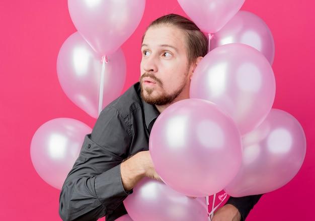 Jonge man viert verjaardagsfeestje met een heleboel ballonnen opzij kijken verrast staande over roze muur Gratis Foto