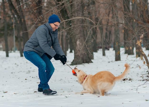 Jonge man waait sneeuwvlokken uit haar handen naar haar hond golden retriever in een winterse dag. vriendschap, huisdier en mens. Premium Foto