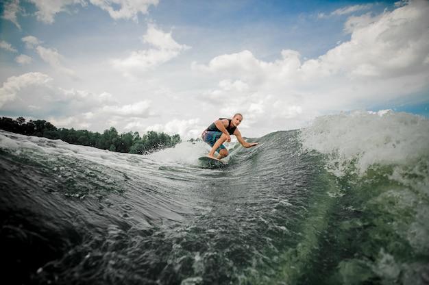 Jonge man wakesurfing op het bord langs de rivier Premium Foto
