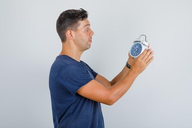 Jonge man wekker instellen in donkerblauw t-shirt en opgewonden kijken. Gratis Foto