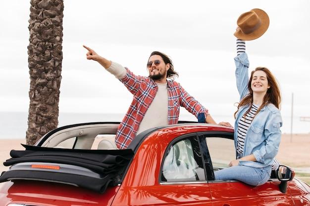 Jonge man wijzend naar de kant in de buurt van de vrouw zwaaiende hand met hoed en leunend uit de auto Gratis Foto