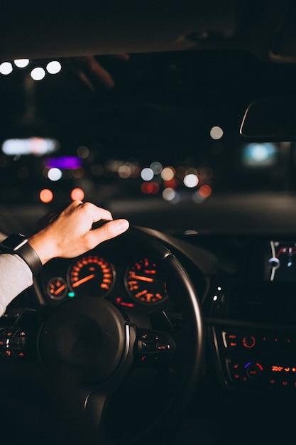 Jonge man zijn auto rijden 's nachts Gratis Foto