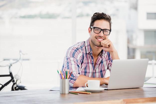 Jonge man zit aan zijn bureau Premium Foto