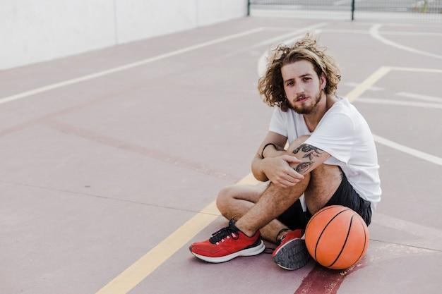 Jonge man zit in de rechtszaal met basketbal Gratis Foto
