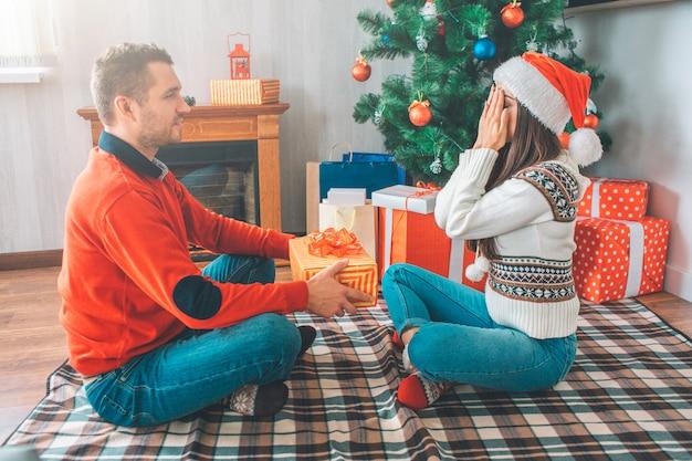 Jonge man zit voor vrouw en kijkt naar haar. hij houdt aanwezig. Premium Foto