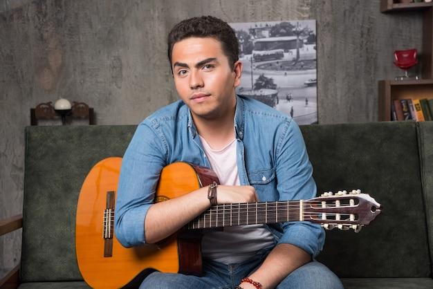 Jonge man zittend op de bank met een mooie gitaar. hoge kwaliteit foto Gratis Foto