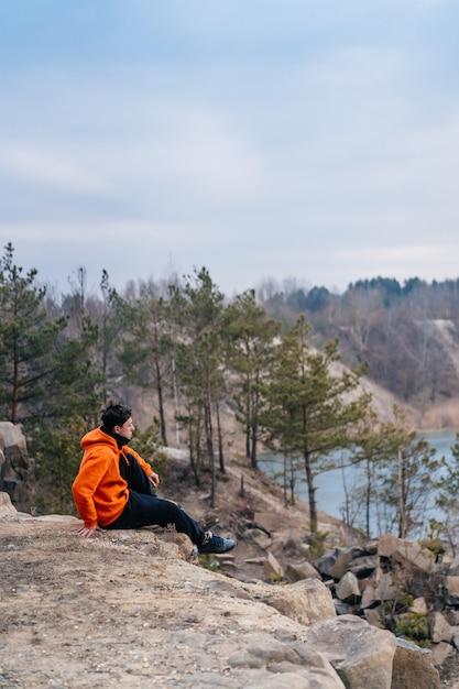 Jonge man zittend op de rand van een klif Gratis Foto