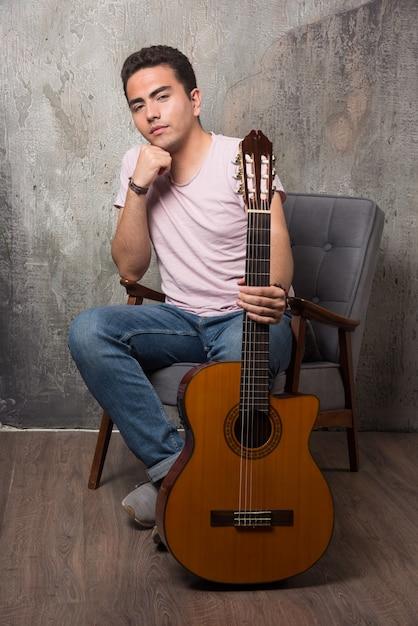 Jonge man zittend op een stoel en met de gitaar. hoge kwaliteit foto Gratis Foto