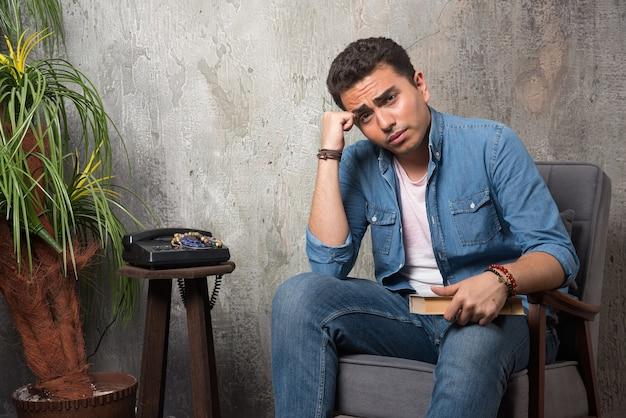 Jonge man zittend op een stoel met boek over marmeren achtergrond. hoge kwaliteit foto Gratis Foto