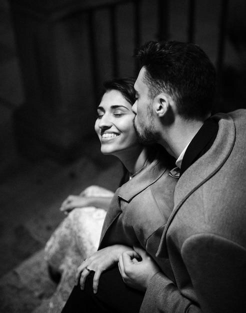Jonge man zoenen gelukkige vrouw op trappen Gratis Foto