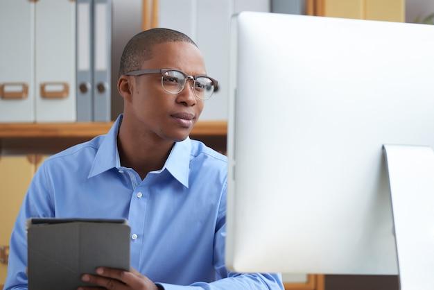 Jonge manager die zakelijk nieuws online leest om op de hoogte te blijven van de nieuwste evenementen in de community Gratis Foto