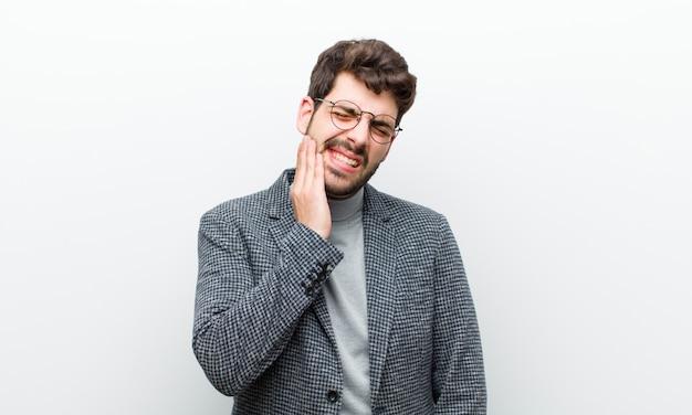 Jonge manager man met wang en pijnlijke kiespijn, ziek, ellendig en ongelukkig, op zoek naar een tandarts witte muur Premium Foto