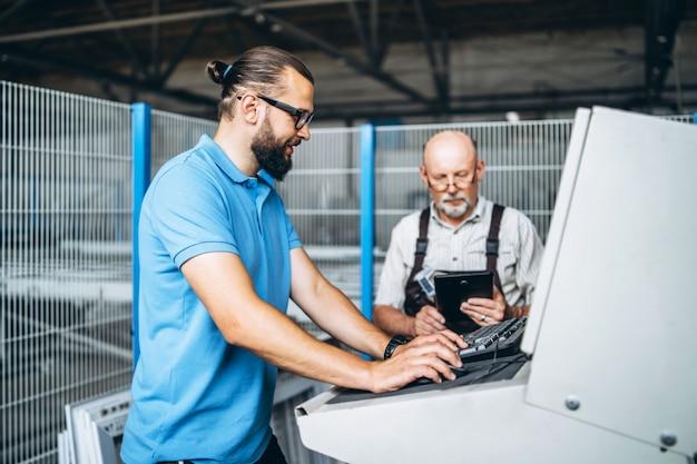 Jonge manager met baard die en werkend proces van volwassen professionele arbeider op de grote fabriek tonen inspecteren. Premium Foto