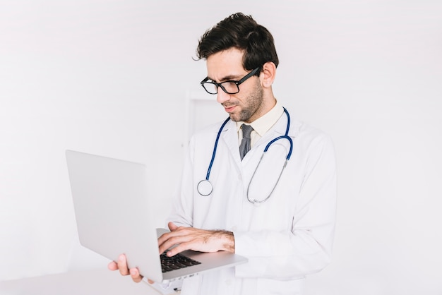 Jonge mannelijke arts die aan laptop werkt Gratis Foto