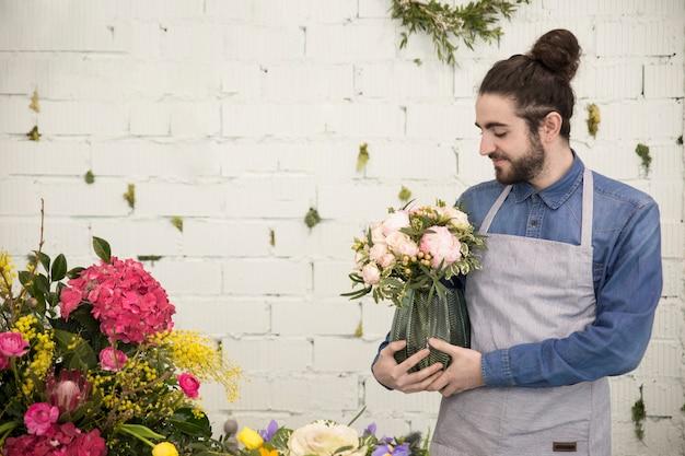Jonge mannelijke bloemist die de bloemenvaas houdt tegen witte bakstenen muur Gratis Foto