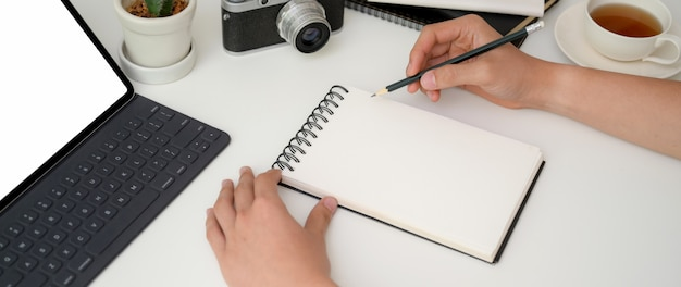 Jonge mannelijke fotograaf korte notitie over notebook Premium Foto
