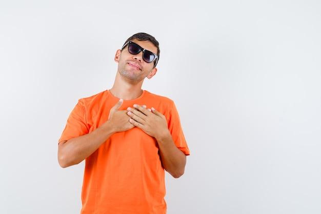 Jonge mannelijke hand in hand op hart in oranje t-shirt en vredig op zoek Gratis Foto