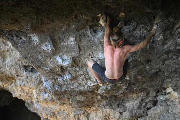 Jonge mannelijke klimmer die een rotswand in een hol bouldert Premium Foto