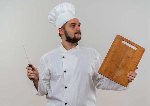 Jonge mannelijke kok in chef-kok het eenvormige mes en scherpe raad die kant bekijken die op witte ruimte wordt geïsoleerd Gratis Foto