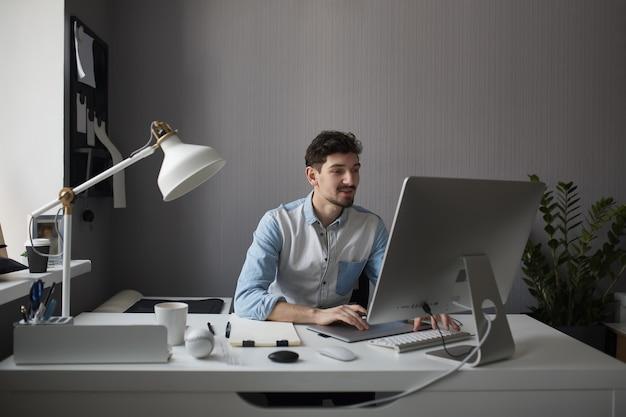 Jonge mannelijke ontwerper die grafisch tablet gebruiken terwijl het werken met com Gratis Foto