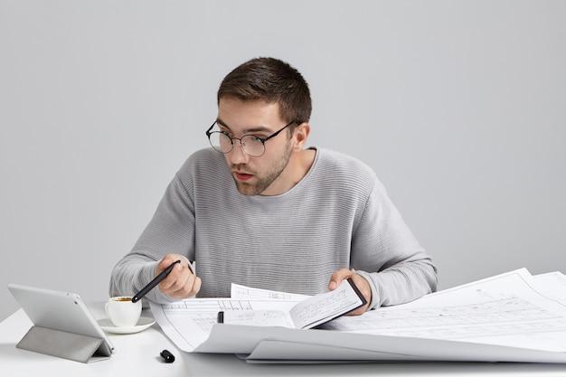 Jonge mannelijke ontwerper staart in het scherm van de tablet, heeft een deadline om het tekenen van schetsen te voltooien, Gratis Foto