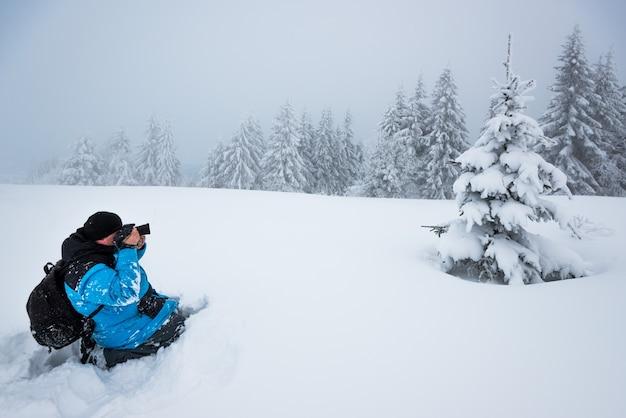 Jonge mannelijke reiziger met rugzak maakt foto's van een prachtige hoge besneeuwde dennenboom in een hoge sneeuwjacht tegen de achtergrond van mist op een ijzige winterdag Premium Foto
