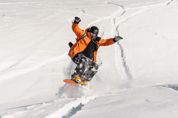 Jonge mannelijke snowboarder in oranje sportkleding die op de sneeuwhelling springt Premium Foto