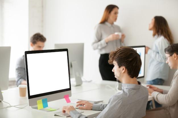 Jonge mannelijke werknemer die aan computer schrijven e-mail in bureau werkt Gratis Foto