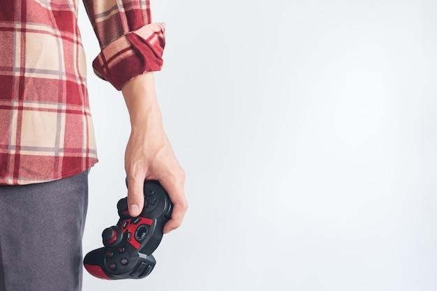 Jonge mannen dragen rode scott-patroonoverhemd hand met joystick-gamepad Premium Foto