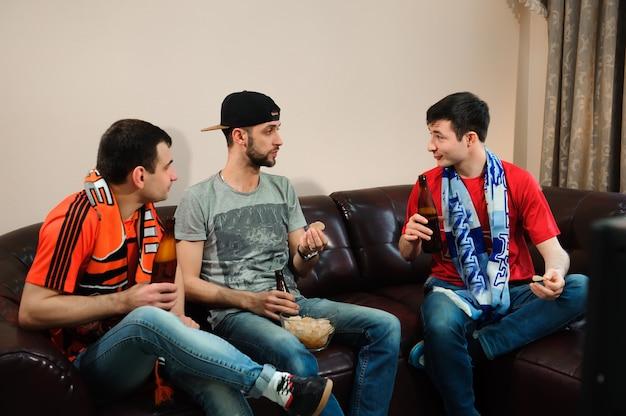 Jonge mannen drinken bier, eten chips en rooten voor voetbal Premium Foto