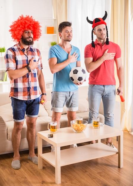 Jonge mannen drinken bier, eten pizza en juichen voor voetbal Premium Foto